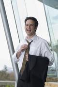 Hispanic businessman loosening necktie Stock Photos