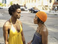African woman talking to friend in urban setting Stock Photos