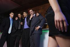 Group of multi-ethnic businessmen looking at woman in bar Stock Photos