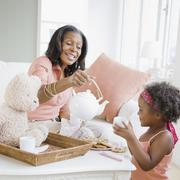 African grandmother having tea party with granddaughter Stock Photos