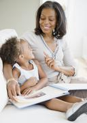 African grandmother looking a photo album with granddaughter Stock Photos