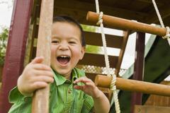 Mixed race boy playing in playground Stock Photos