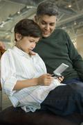 Latinalaisamerikkalainen isä katsomassa poika pelaa videopeli Kuvituskuvat