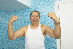 Hispanic man flexing his biceps in bathroom Stock Photos