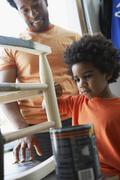 Afrikkalainen isä katsomassa poika maali keinutuoli Kuvituskuvat