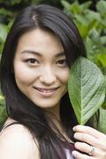 Smiling Japanese woman holding leaf Stock Photos