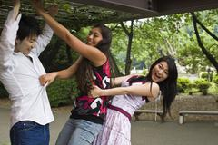 Japanese friends playing outdoors - stock photo