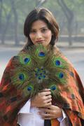 Indian woman holding peacock feather fan - stock photo