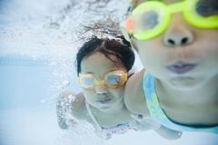 Hispanic girls swimming underwater in pool Stock Photos