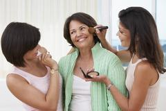 Sisters giving mother a makeover Stock Photos