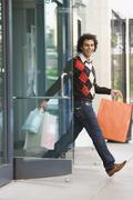 Middle Eastern man leaving store with shopping bags - stock photo