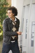 Middle Eastern man at ATM - stock photo