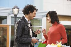 Middle Eastern man giving girlfriend credit card - stock photo