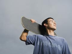 Mixed race teenager standing with skateboard Stock Photos