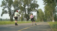 Man and Woman Are Riding on Roller Skates in the Park Stock Footage