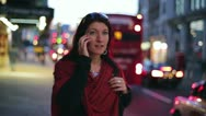 Woman talking on cellphone in the evening, steadicam shot HD Stock Footage