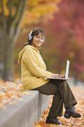 Hispanic woman using laptop outdoors with headphones Stock Photos