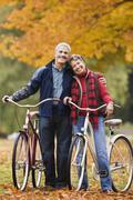 Afrikkalainen pari seisoo polkupyörien puistossa syksyllä Kuvituskuvat