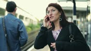 Woman talking on cellphone on train station, steadicam shot HD Stock Footage
