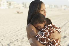 Mixed race mother holding daughter at beach - stock photo