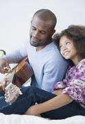 Stock Photo of African father playing guitar for daughter