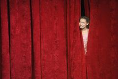 Mixed race person hiding behind stage curtain - stock photo