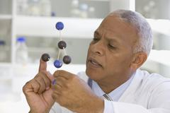 African scientist viewing molecule model in laboratory Stock Photos