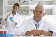 African scientist in laboratory with co-worker in background Stock Photos