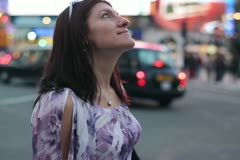 Young woman standing and looking around on Piccadilly Circus NTSC Stock Footage