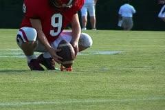 Football player setting football on tee preparing to kick - stock footage
