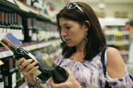Young woman checking wine in supermarket, steadicam shot NTSC Stock Footage