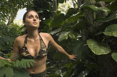 Hispanic woman wearing camouflage bikini in jungle - stock photo