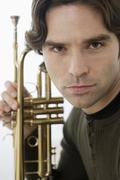 Close up of hispanic man holding trumpet Stock Photos