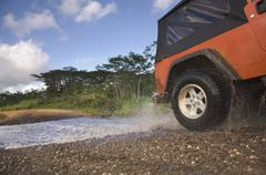 4x4 driving through water on remote road Stock Photos