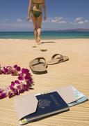 Woman walking away from passport and sandals on beach Stock Photos