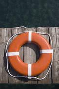 Round life preserver on wooden dock Stock Photos