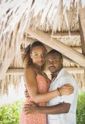 african american couple hugging in grass hut - stock photo