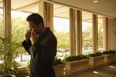 Hispanic businessman talking on cell phone Stock Photos