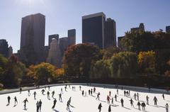 Crowd of people ice skating in urban skating rink Stock Photos
