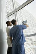 Multi-ethnic doctor and nurse reviewing x-ray by window Stock Photos
