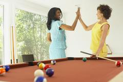 Multi-ethnic friends playing pool Stock Photos