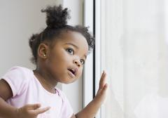 African american girl looking out window Stock Photos