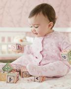 Mixed race baby girl playing with alphabet blocks Stock Photos