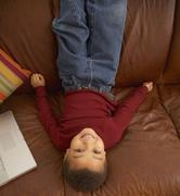Mixed race boy laying upside down on couch Stock Photos