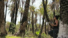 Girl with ipad in palmtrees Stock Footage
