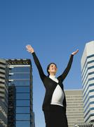 Pregnant middle eastern woman with arms raised outdoors Stock Photos