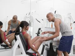 African man helping woman on exercise equipment Stock Photos
