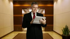Businessman holds tablet that shows success Stock Footage