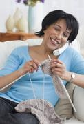 African woman talking on the phone and knitting Stock Photos