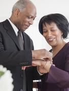 african man attaching bracelet for wife - stock photo